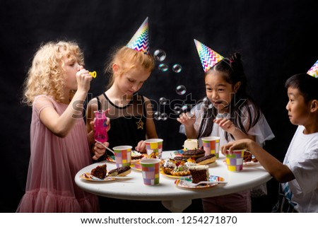 Group of happy children blowing soap bubbles during birthday. closeup photo. happiness, magic bubbles, entertainment. studio shot