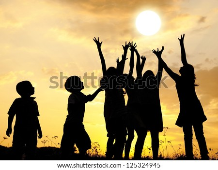 Group of happy children catching sun with their arms