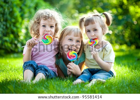 Group of happy children eating fruit drops outdoors in spring park