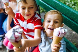 Group of happy children eating ice cream together outdoor. Photo of happy blond girls with two handsome boys sitting on the bench and smiling at camera.