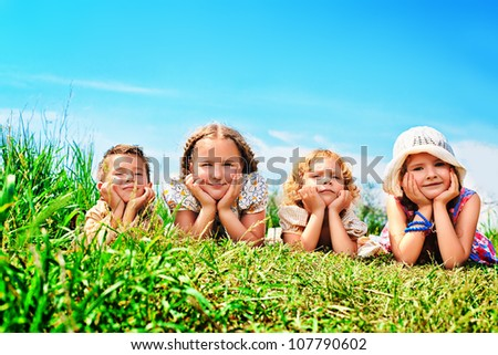 Group of happy children having a rest together outdoors.