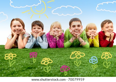 Group of happy children lying on a green grass