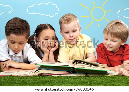 Group of happy children lying on a green grass and reading books - stock photo