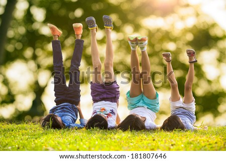Group of happy children lying on green grass outdoors in spring park #181807646
