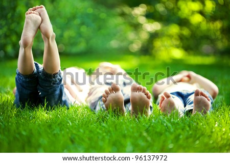 Group of happy children lying on green grass outdoors in spring park - stock photo