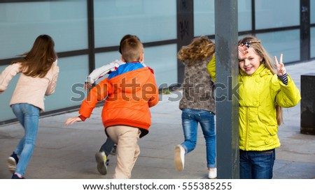 Group of happy children playing at Hide-and-seek outdoors