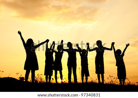 Group of happy children playing at summer sunset in nature