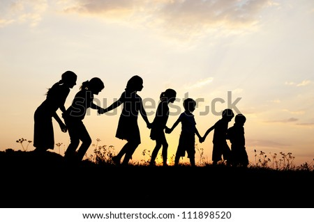 Group of happy children playing on meadow at sunset