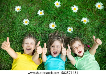 Group of happy children playing outdoors. Kids having fun in spring park. Friends lying on green grass. Top view portrait #583571431