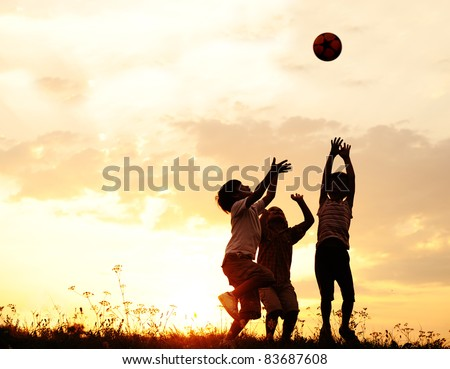 Group of happy children playing with ball on meadow, sunset, summertime