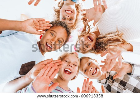 Group of happy children waving at the camera #606913358
