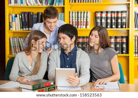 Group of happy college friends with digital tablet studying in library