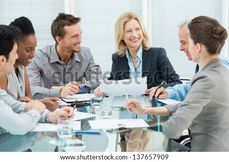Group Of Happy Coworkers Discussing In Conference Room - stock photo