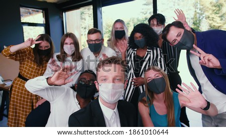 Group of happy diverse business colleagues posing, waving for selfie photo in masks against COVID-19 at modern office. Stockfoto ©