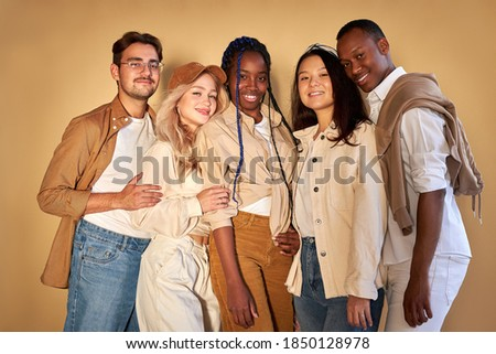 group of happy diverse young men and women isolated on beige background, five friendly mixed race models, wear stylish casual clothes posing at camera Сток-фото ©