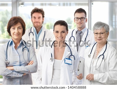 Group of happy doctors in hospital corridor portrait