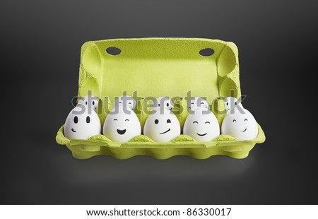 Group of happy eggs with smiling faces representing a social network. Ten white eggs in a carton box. On a black background