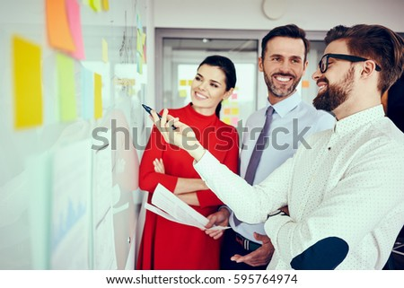Group of happy executives, employees discussing new project on whiteboard at office