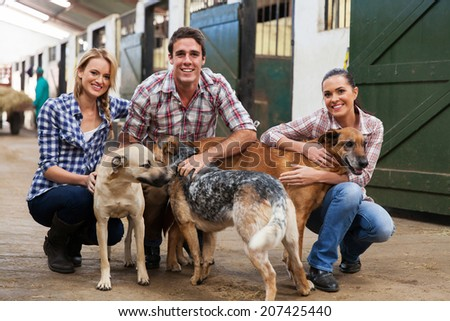 group of happy farm workers with pet dogs in stables