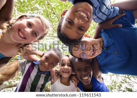Group of happy female and male kids having fun and hugging around the camera. Low angle view