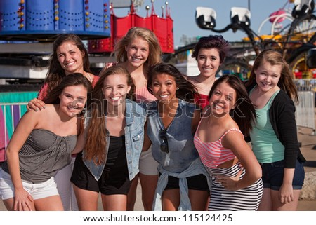 Group of 8 happy female teens at an amusement park