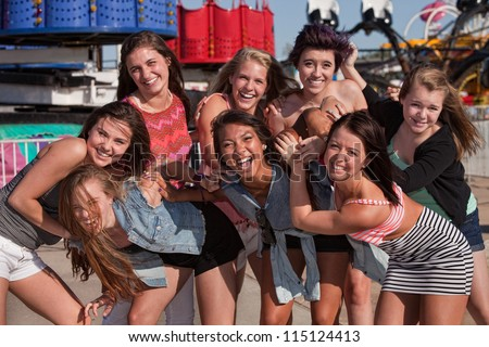 Group of 8 happy female teens together at a carnival