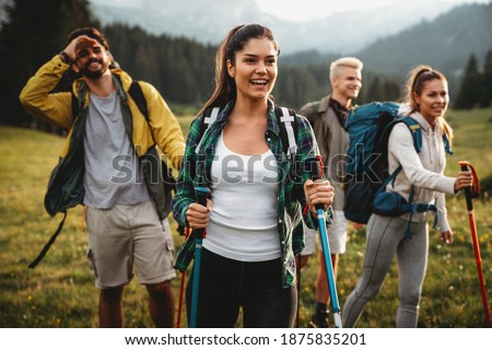Group of happy fit friends hiking, trekking together outdoor nature