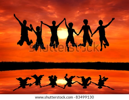 group of happy freedom men and women friends jumping with joy at sunrise silhouetted