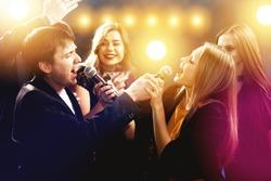 Group of happy friends are having fun, singing and dancing in karaoke club