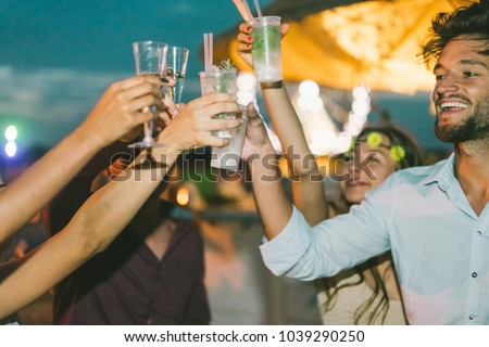 Group of happy friends cheering with cocktails at beach after sunset party - Trendy people having fun in summer holidays - Soft focus on right man eye - Fun, summer and youth lifestyle concept