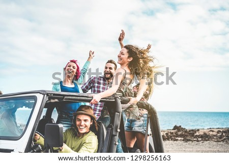 Group of happy friends doing excursion on desert in convertible 4x4 car - Young people having fun traveling together - Friendship, tour, youth lifestyle and vacation concept - Focus on right girl face