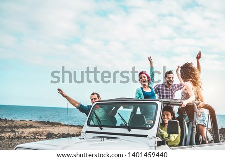 Group of happy friends doing excursion on desert in convertible 4x4 car - Young people having fun traveling together - Friendship, tour, youth lifestyle and vacation concept - Focus on right guys #1401459440