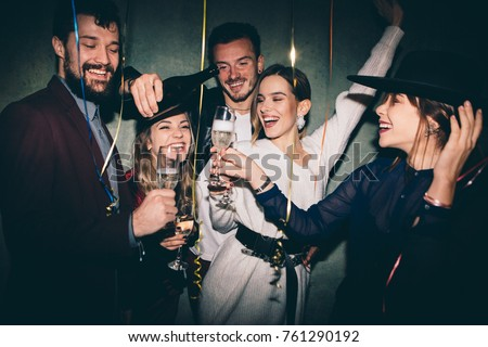 Group of happy friends drinking champagne and celebrating New Year. New year party. Birthday party #761290192