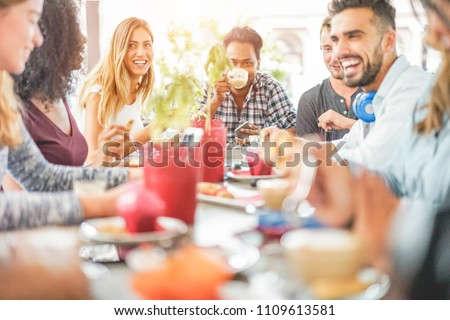 Group of happy friends drinking coffee and cappuccino at bar cafe - Young millennials people eating breakfast and drinking hot beverages - Friendship, youth and food concept - Focus on left blond girl