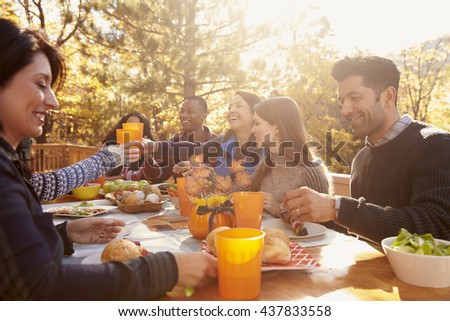 Group of happy friends eat and drink at a table at a barbecue