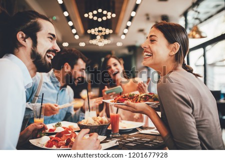 Group of Happy friends having breakfast in the restaurant