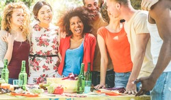 Group of happy friends having fun at barbecue party outdoor in nature - Young multicultural people making bbq dinner - Youth lifestyle, food and friendship concept - Main focus on left guys