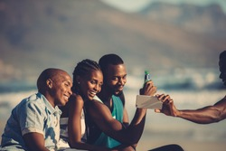 Group of happy friends having fun together and taking selfie using mobile phone. Self portrait at beach party.
