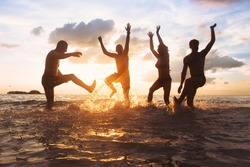 group of happy friends having fun together on the beach at sunset, jumping and dancing with water splash in the sea, silhouettes of people