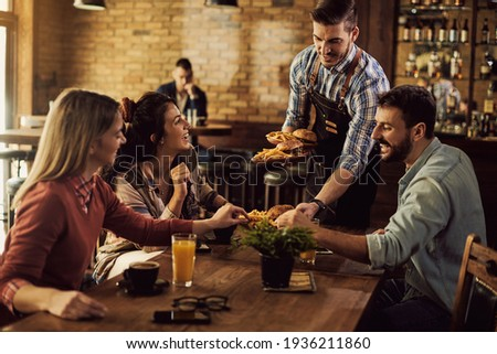 Group of happy friends having fun while waiter is serving them food in a pub.  Stock photo ©