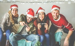 Group of happy friends having fun with video games console on christmas time - Young millennial people playing and laughing on winter holiday with vintage light on background - Focus on right man face