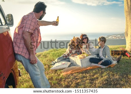 Group of happy friends hippie style, eats on the meadow. Smiling people toast with bottles of beer with the sea in background. Family doing a flower power mood pic-nic in a spring morning with old van