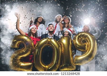 467d307e26f4e Group of happy friends holding golden balloons in form of 2019 at New Year s  Eve party