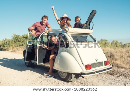 Group of happy friends in a car at sunset in summer.