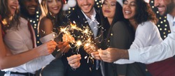 Group of happy friends in New Year eve with sparkling bengal lights, panorama, closeup