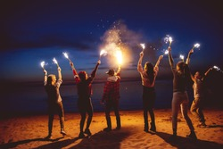 Group of happy friends is having fun or celebrating something with signal fires at evening beach