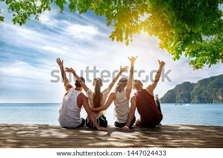 Group of happy friends is sitting and hugging at idyllic sea beach. Phi-phi island, Krabi, Thailand