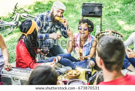 Group of happy friends joking and having fun at barbecue picnic outdoor - Young diverse culture students enjoying dinner in nature park - Youth, summer ,friendship concept - Focus on afro girl