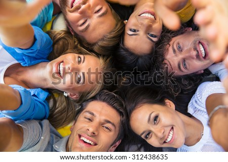 Group of happy friends lying together in a circle #312438635