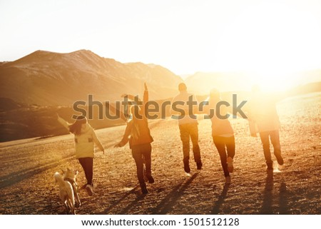Group of happy friends or travellers is having fun in sunset light. Travel together concept #1501512128